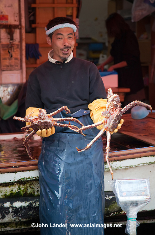 Crab vendor at fish market. Products on sale include various types of fresh seafood such as crabs, salmon eggs, and sea urchin. Several fish restaurants can be found in the market area, offering fresh seafood if your stomach is up to it.
