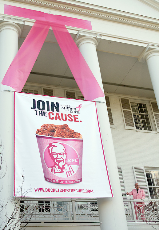 "The KFC Colonel Bob Thompson helps hang a pink ribbon as KFC's ""White House"" global headquarters ""goes pink"" Friday, April 9, 2010 in Louisville, Ky., as part of a brand-wide color makeover to help launch their Buckets For a Cure(TM) campaign, aimed at raising both money and awareness for breast cancer. (Photo by Brian Bohannon)."