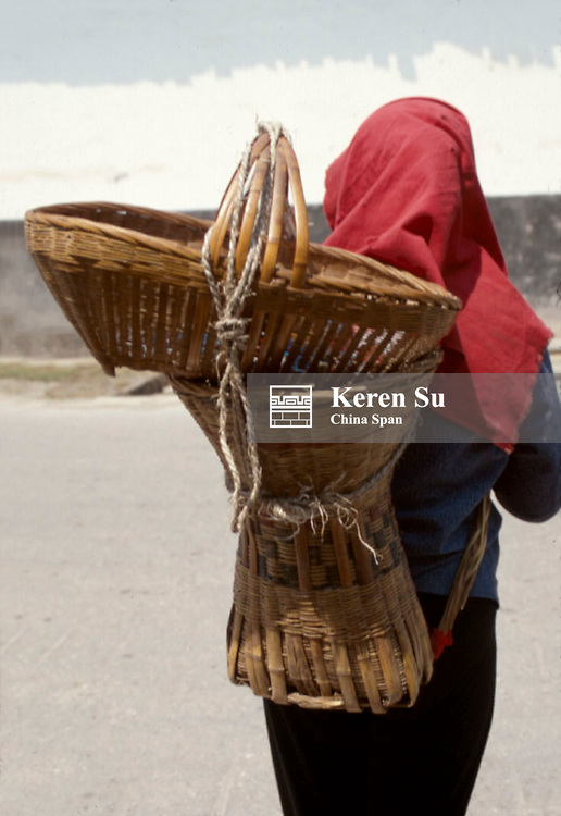Local farmer carrying bamboo basket at the back along the Three Gorges of the Yangtze River, China
