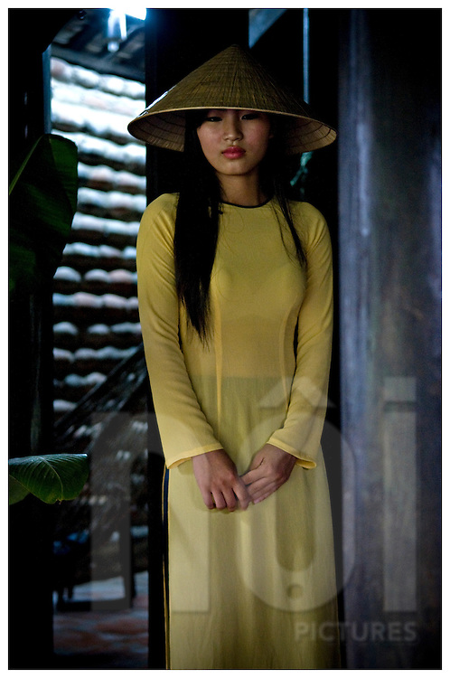 Beauty portrait of a vietnamese woman standing and leaning against a wooden pillar. She wears traditional outfit Ao Dai and a conical hat. Khanh Hoa area, Vietnam, Asia