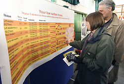 Interactive display at a Low Carbon Zone public meeting in Muswell Hill - couple placing stickers to denote interest in draft proofing London UK