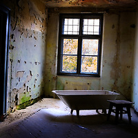 Old bathroom with stool in derelict room near window