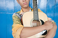 Mid section of a teenage boy with guitar against wood paneling