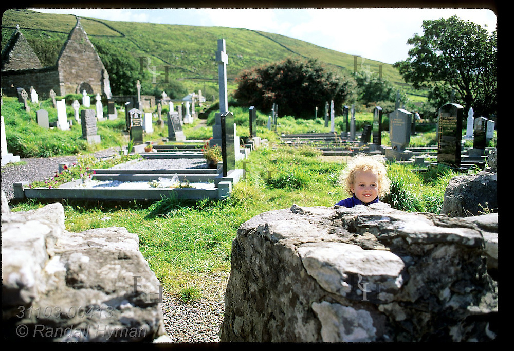 Little girl peeks over stone wall in cemetery at Kilmalkedar Church on the Dingle Peninsula in southwest Ireland.