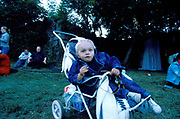A little boy dressed in a denim jacket and jeans sitting in a pushchair. Quart festival, Kristiansands Norway 2000