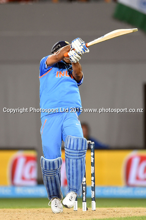 Indian captain Mahendra Singh Dhoni finishes the game off with a six during the ICC Cricket World Cup match between India and Zimbabwe at Eden Park in Auckland, New Zealand. Saturday 14 March 2015. Copyright Photo: Raghavan Venugopal / www.photosport.co.nz