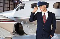 Portrait of handsome young pilot standing in front of private airplane