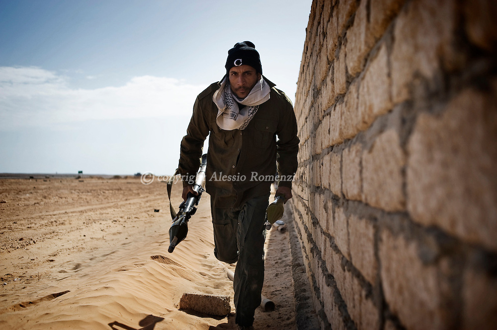 LIBYA, SIDRA : Libyan rebel take cover from incoming shells in Sidra on March 10, 2011 as Libyan strongman Moamer Kadhafi and rebels seeking his downfall battled each other on the military and diplomatic fronts.ALESSIO ROMENZI
