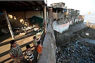 A mother and her three children wait for her husband to arrive from a morning fishing trip  The small fishing village of Machimaar Nagar struggles to hold on as the explosive growth of Mumbai begins to encroach on its space.