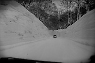 A car dwarfed by the walls of snow crowding the road after more than 5 meters (16 feet) of snow fell this winter in the mountains of Aomori Prefecture.  Japan.