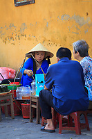 Locals enjoy a meal at a roadside food stall in the old town of Hoi An, Vietnam
