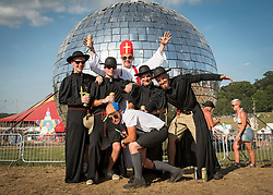 Festival goers wearing fancy dress in front of the giant glitter ball at Bestival 2018 Lulworth Castle - Wareham. Picture date: Saturday 4th August 2018. Photo credit should read: David Jensen/EMPICS Entertainment