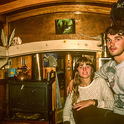 We had a small woodstove, for cooking and heating, which required very small pieces of wood. On the starboard side of the boat there was a bunker for wood. Much chopping, splitting and sawing was required to make kindling and a sufficient supply of short lengths of wood to keep the stove going. Because it was such a small space we could get smoked out very quickly. There was a little wooden stool next to the stove, which we referred to as the hot seat. We enjoyed having social gatherings on the boat, and they were very intimate cheek to jowl occasions because of the cramped space. The coach roof was supported by very stout laminated ash beams, which inflicted many painful bruises on my head and on anybody else who was forgetful of the limited overhead clearance. It was my first experience living on a boat and I absolutely loved it.