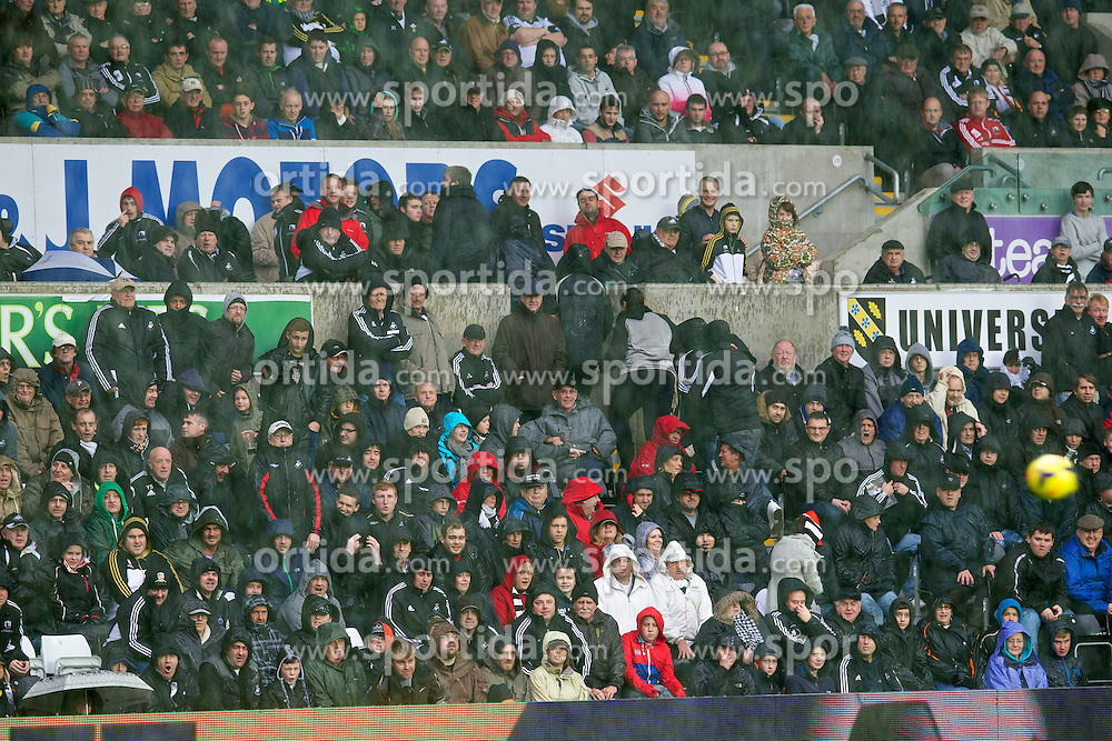 27.10.2013, Liberty Stadion, Swansea, ENG, Premier League, Swansea City vs West Ham United, 09. Runde, im Bild Swansea City supporters take cover from the heavy rain // during the English Premier League 09th round match between Swansea City AFC and West Ham United at the Liberty Stadion in Swansea, Great Britain on 2013/10/27. EXPA Pictures &copy; 2013, PhotoCredit: EXPA/ Propagandaphoto/ David Rawcliffe<br /> <br /> *****ATTENTION - OUT of ENG, GBR*****