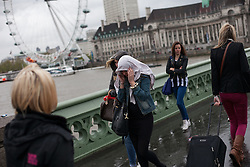 Tourist cover themselves with clothe to protect their hear  amid rain and wind, at Westminster Bridge, London, UK, 14th May, 2013. Photo by: Daniel Leal-Olivas / i-Images