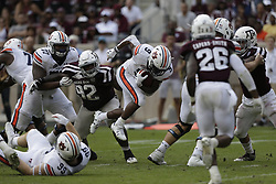 Auburn running back Kam Martin (9) breaks away from a tackle attempt by Texas A&M defensive lineman Zaycoven Henderson (92) during the fourth quarter of an NCAA college football game on Saturday, Nov. 4, 2017, in College Station, Texas. (AP Photo/Sam Craft)