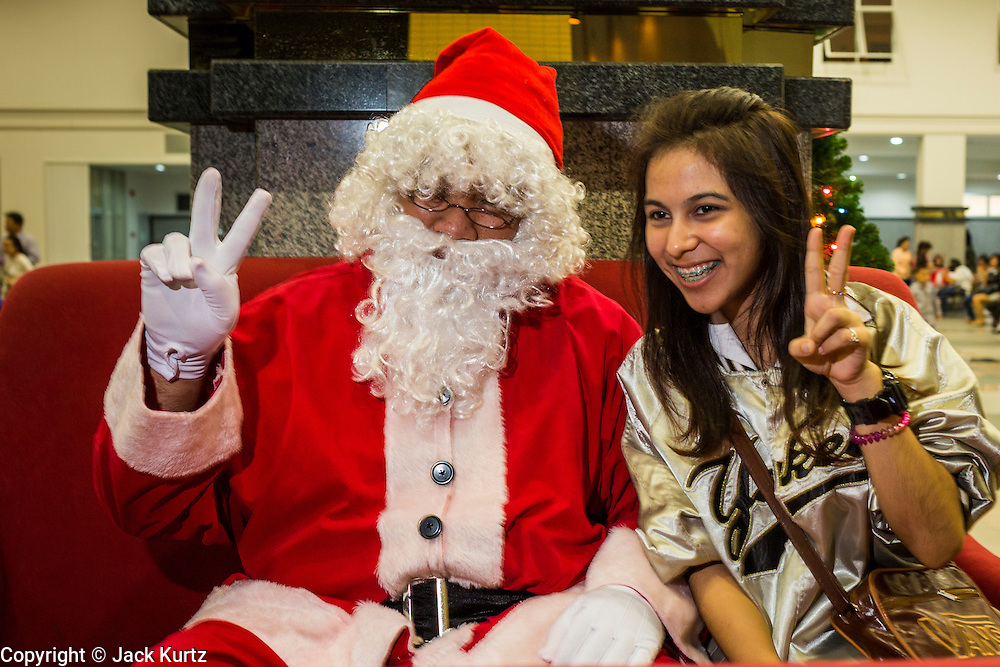24 DECEMBER 2013 - BANGKOK, THAILAND: A Thai woman poses with Santa Claus during Christmas observances at Holy Redeemer Church in Bangkok. Thailand is predominantly Buddhist but Christmas is widely celebrated throughout the country. Buddhists mark the day with secular gift giving but there are about 300,000 Catholics in Thailand who celebrate religious Christmas. Catholics first came to Thailand (then Siam) in 1567 as chaplain for Portuguese mercenaries in the employ of the Siamese monarchy. There has been a continuous Catholic presence in Thailand since then.   PHOTO BY JACK KURTZ