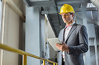 Young businessman using tablet computer in industry