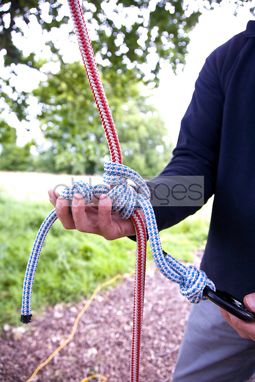 Close up of climber hands holding and checking climbing rope