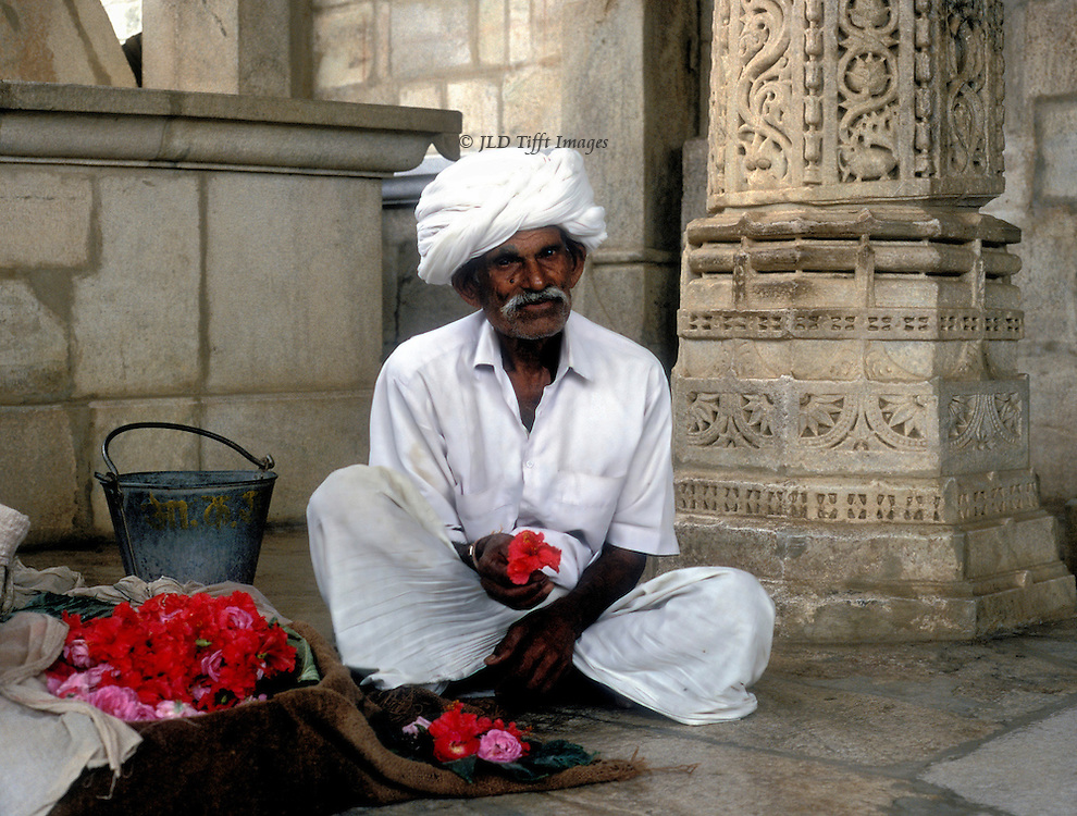 Flower seller outside the 15th century Jain temple at Ranakhpur, seated cross legged, offering flowers for sale.