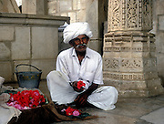 Flower seller outside the 15th century Jain temple at Ranakhpur, seated cross legged, offering flowers for sale.