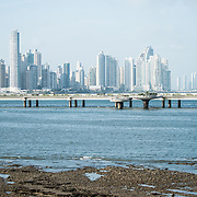 Low tide on the rocky, flat shoreline on the waterfront of Panama City, Panama, on Panama Bay, looking past the Coast Beltway (Cinta Costera III)  towards Punta Paitilla in the background.