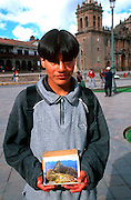 PERU, HIGHLANDS, CUZCO ancient capital of the Incas; the Plaza de  Armas with a young boy selling postcards