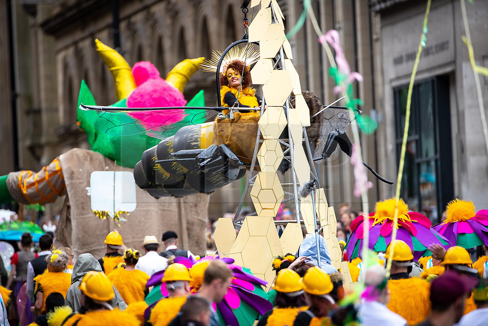© Licensed to London News Pictures . 17/06/2018. Manchester , UK . A woman flies a bee (the symbol of Manchester) above the crowd . The 2018 Manchester Day parade , celebrating Manchester's cultural and social life and diversity, passes through Manchester City Centre . Photo credit : Joel Goodman/LNP