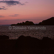 Sunset afterglow at Shirasaki is coloring the cloud-filled sky behind and above the limestone rocks to rosy colors at the cape of Shirasaki, creating a beautiful marine landscape at sunset.