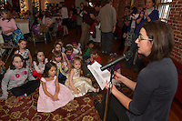 "Jocelyn Sprague and Gracie Dube listen as Author Jennifer Carson reads a chapter from ""Hapenny Magick"" during Lakes Region Community Services sponsored Children's Authors Tea at the Belknap Mill Tuesday evening.   (Karen Bobotas/for the Laconia Daily Sun)"