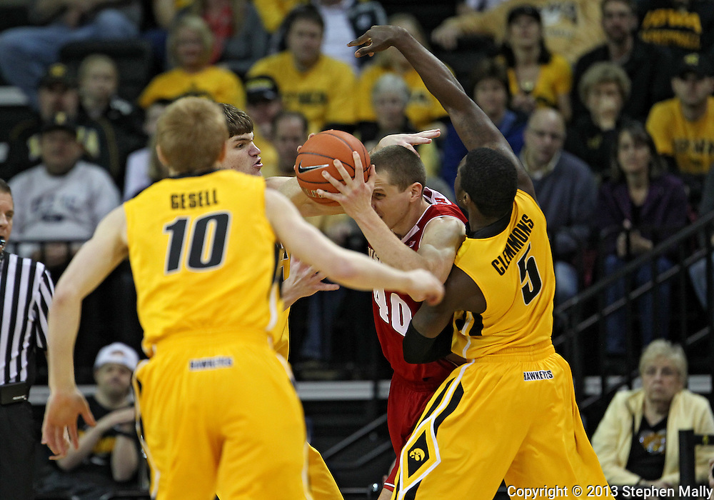 January 19 2013: Wisconsin Badgers forward/center Jared Berggren (40) tries to keep the ball away from Iowa Hawkeyes center Adam Woodbury (34) and guard Anthony Clemmons (5) as Iowa Hawkeyes guard Mike Gesell (10) looks on during the first half of the NCAA basketball game between the Wisconsin Badgers and the Iowa Hawkeyes at Carver-Hawkeye Arena in Iowa City, Iowa on Sautrday January 19 2013. Iowa defeated Wisconsin 70-66.