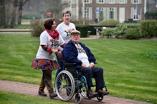 Nederland, Arnhem, 18-03-2014 Bij zorginstelling Vreedenhoff werd dinsdagmiddag een protestactie gehouden. Werknemers onderbreken het werk voor 1 minuut en maken een foto, groepsfoto die ze opsturen aan de vakbond Abva Kabo, FNV. Een van de ouderen, bewoners, was solidair en deed mee.Foto: Flip Franssen