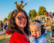 A family come as characters from Alice in Wonderland. The sun begins to set on the first main day - The 2018 Latitude Festival, Henham Park. Suffolk 13 July 2018