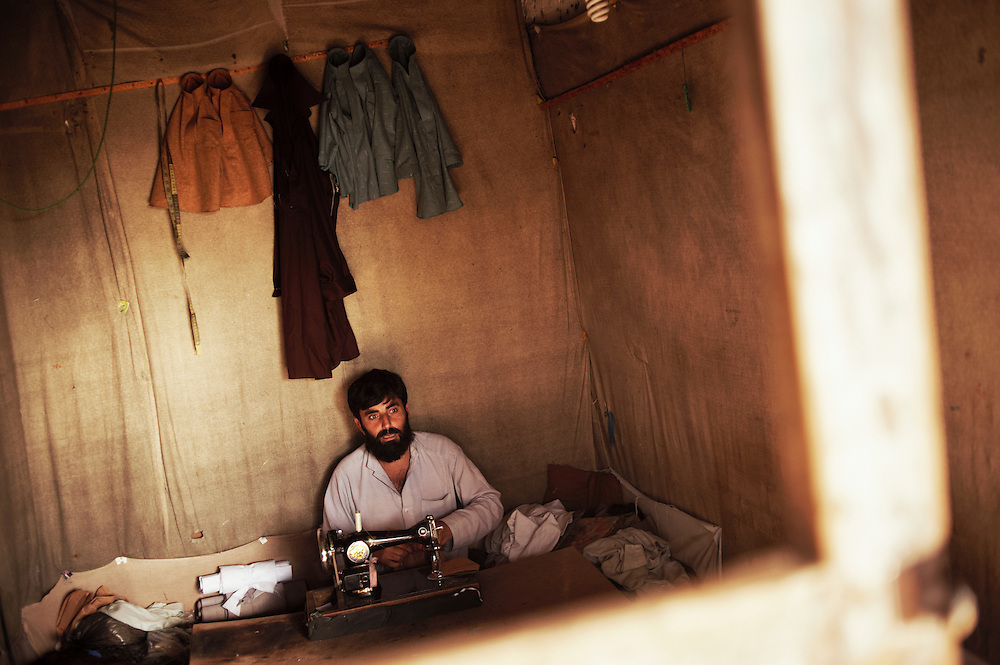 Pakistan/ Afghan refugees/ A tailor sews in his storefront at Khazana refugee camp, Peshawar.  The camp was established when refugees flooded across the border from Afghanistan during the 1979 Soviet occupation. The refugee camp has a population of 2500 and during the 2010 floods that swept through Pakistan most families were affected. The majority of people rebuilt their houses after the floods with their own resources. The most vulnerable also received support from UNHCR for reconstruction. UNHCR/Sam Phelps/ November 2011 UNHCR/Sam Phelps/ November 2011.