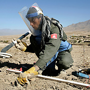 A member of a Halo Trust team searches for mines on the outskirts of a village. Afghanistan remains one of the most heavily mined countries in the world. A mine clearance team from the Halo Trust have been working for more than a year in the small village of Kohe Safi and have removed 800 mines and 118 unexploded bombs. Kohe Safi, Afghanistan on the 1st of November 2007..Throughout the country the Halo Trust alone is working to clear 90 million square meters of mine fields containing some 640,000 mines, they estimate it will take them 18 years to complete this task..A break through in mine detection not seen since  World War II is due to speed things up in the coming year when Halo become the first civllian organisation to use H-STAMIDS (The Handheld Stand-Off Mine Detection System) a new combination tool with a metal detector and ground penetrating radar system. The H-STAMIDS remain classified and during recent trails in Afghanistan the device had to be returned to the US military at the end of each day. The new equipment should make mine clearance 2-3 times faster...