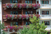 red and White flowers in window boxes in the facade of a typical Tirolian house now hotel. Photographed in Neustift, Tirol, Austria
