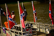 Rick Marr stands on a pontoon boat decked with confederate flags and a horn for the 10th Annual Redneck Fishin' Tournament held Saturday, Sept. 5, 2015, in Bath, ILL. The only fishing tournament where poles are not allowed and you must catch the Asian Carp with a net or your hands as they fly through the air. This year 5,839 if the invasive species were removed from the Illinois River during the tournament. Photography by Rob Hart