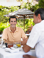 Two men having conversation at table laughing selective focus