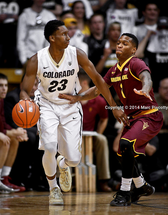 SHOT 2/19/14 10:19:06 PM - Colorado's Jaron Hopkins #23 looks to pass in front of Arizona State's Jahii Carson #1 during their regular season Pac-12 basketball game at the Coors Events Center in Boulder, Co. Colorado won the game 61-52.<br /> (Photo by Marc Piscotty / &copy; 2014)