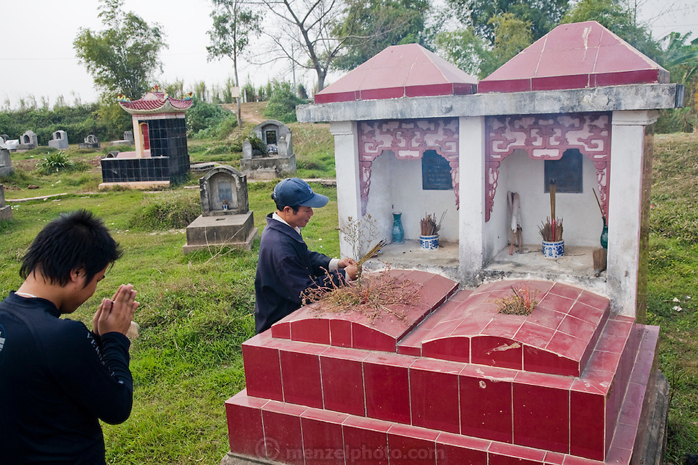 Two grandsons say a prayer at the grave of their grandfather near Tho Quang Village, Vietnam.