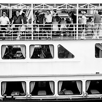 MIRAFLORES LOCKS - PANAMA CANAL<br /> Photography by Aaron Sosa<br /> Panama City, Panama 2012<br /> (Copyright © Aaron Sosa)<br /> <br /> One of the boats that do tours full of tourists who pass through the Panama Canal.<br /> <br /> The Panama Canal is an 77.1-kilometre (48 mi) ship canal in Panama that connects the Atlantic Ocean (via the Caribbean Sea) to the Pacific Ocean. The canal cuts across the Isthmus of Panama and is a key conduit for international maritime trade. There are locks at each end to lift ships up to Lake Gatun (26m (85ft) above sea-level) which was used to reduce the amount of work required for a sea-level connection. The current locks are 33.5m (110ft) wide although new larger ones are proposed.<br /> <br /> Work on the canal, which began in 1881, was completed in 1914, making it no longer necessary for ships to sail the lengthy Cape Horn route around the southernmost tip of South America (via the Drake Passage) or to navigate the dangerous waters of the Strait of Magellan. One of the largest and most difficult engineering projects ever undertaken, the Panama Canal shortcut made it possible for ships to travel between the Atlantic and Pacific Oceans in half the time previously required. The shorter, faster, safer route to the U.S. West Coast and to nations in and along the Pacific Ocean allowed those places to become more integrated with the world economy.
