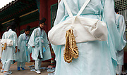 "Traditional straw shoes, or jipsin, hang from the bags of students in traditional scholars' costume as they arrive at Myeongnyundang, a lecture hall at a Confucian shrine at Sungkyunkwan University in Seoul May 11, 2012. The high school students are from the port city of Busan and were taking part in a re-enactment of the traditional state examinations,""Gwageo"". The practice of holding ""Gwageo"" to select government officials began in Korea in 788 and was abrogated in 1894. Jipsin were commonly worn by farmers, common people and scholars in ancient times in Korea until the early twentieth century. Photo by Lee Jae-Won (SOUTH KOREA) www.leejaewonpix.com/"