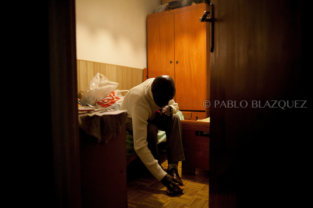 Luis Mendes clean his shoes the night before he faces eviction from his home on January 10 of 2011 in Torrejon de Ardoz, Madrid, Spain. .Luis Mendes is currently an unemployed builder, 45 years old, from Guinea Bissau, and has a wife and 8 children to maintain in Senegal. He lives at his home in Torrejon De Ardoz, Madrid, with his brothers. .Today he is facing a second eviction attempt as he stopped paying the mortgage to Bankia Bank when lost his job in 2009 during the economic crisis. He had to choose between feeding his children or paying the bank. At the moment, he cannot even send money anymore to his family and if he losses his current house, he would gain a live-long debt. He has tried to negotiate with the bank to reach a different solution, by paying a lower monthly fee, but up to now there was no agreement for it..This is also case of many people in Spain that are losing their homes every-days and also gaining debts to banks..According to details of the General Council of the Judiciary, in Madrid there are 40 evictions every-days.