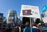 A sign calling for the impeachment of President Donald Trump at the Vote Out the Scandal rally at Hachiko Square, Shibuya, Tokyo, Japan. Sunday November 5th 2017. Timed to coincide with President Trumps visit to Japan, About 120 Americans living in Japan and some local Japanese  protested together from 2pm to 4pm to encourage US citizens to register to vote in future elections and call on the US government to honour it responsibilities to the American people,.