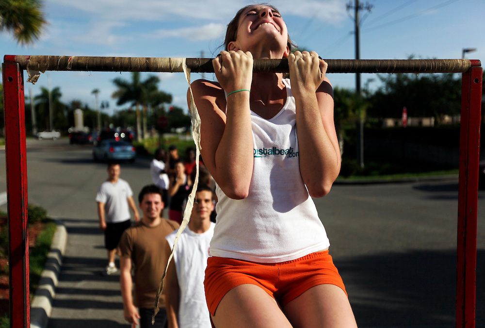 "Elaine Neal strains to keep her chin above the bar in a flexed arm hang during a Marine Corps Initial Strength Test at the recruiting sub-station off Pine Ridge Road in Naples on June 3, 2009. The minimum for a female Marine in the flexed arm hang is 15 seconds, but Neal finished with a personal best of 70 seconds. Neal said that for a lot of activities she generally loses interest after time and ends up quitting, but the choice to be in the Marines is different. ""That's another reason why I really like [the Marines], because I'm trying my best on something,"" Neal said. Greg Kahn/Staff"