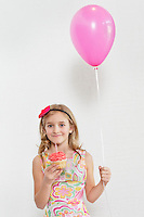 Portrait of happy girl holding cupcake and party balloon over colored background