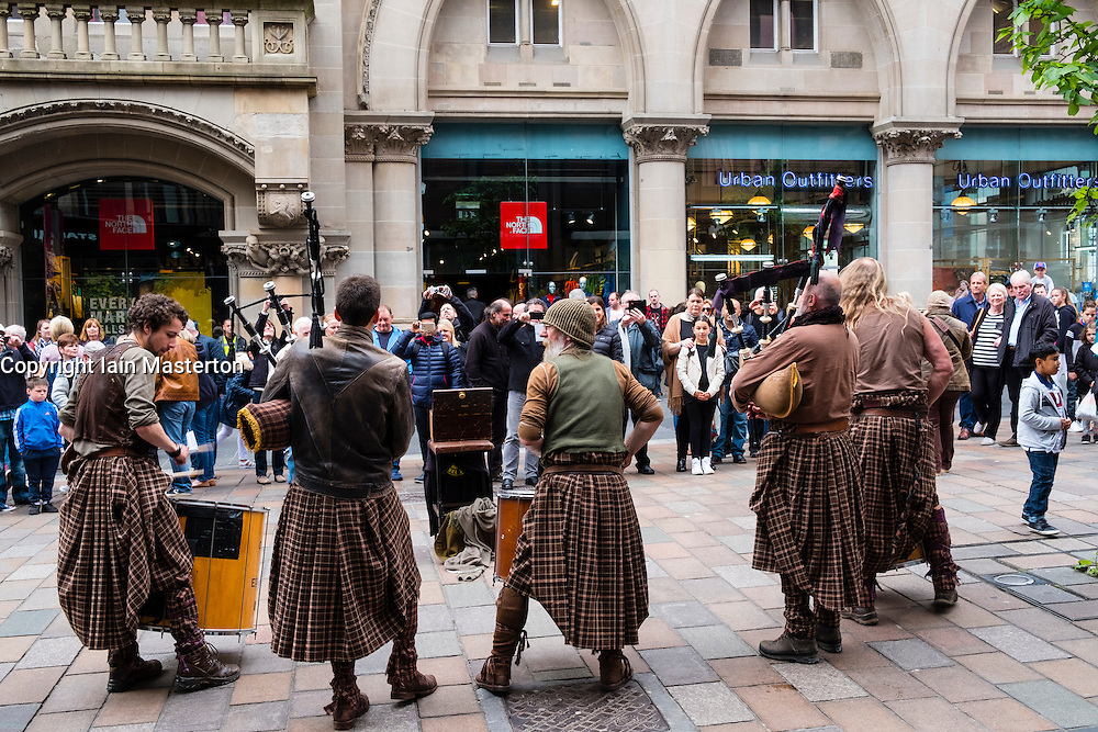 Scottish street buskers in kilts playing traditional music on Buchanan Street in Glasgow Scotland United Kingdom