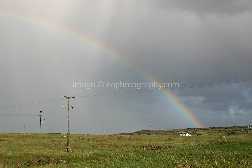 Rainbow against grey cloudy sky on Inis Mor the Aran Islands, Connemara, County Galway, Ireland. Winter and autumn weather conditions, a rainy day in the gaelteacht area.