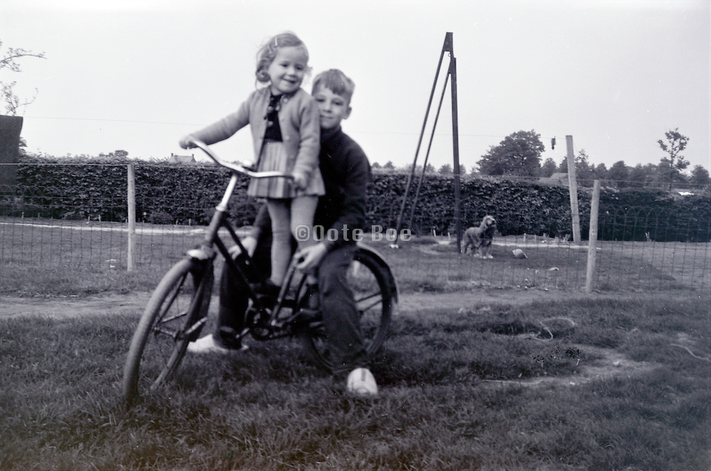brother with sister posing on a bicycle 1960s