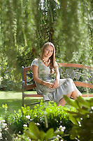 Portrait of beautiful young woman sitting on bench in park